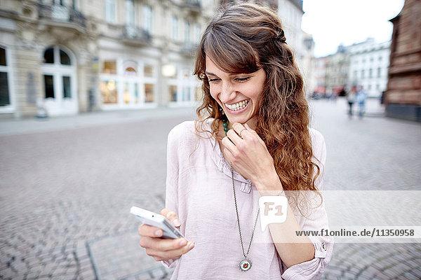 Fröhliche junge Frau in der Stadt schaut auf ihr Handy