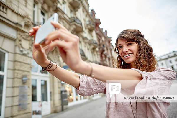 Lächelnde junge Frau in der Stadt macht ein Selfie