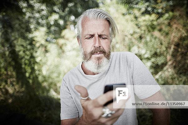 Reifer Mann mit Vollbart im Freien schaut auf Handy