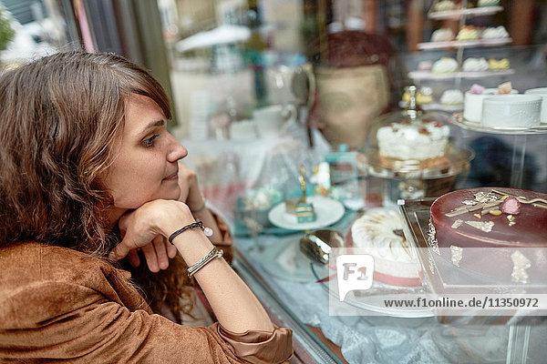 Junges Frau schaut in die Auslage einer Konditorei
