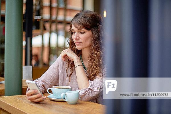 Junge Frau in einem Cafe schaut auf ihr Handy
