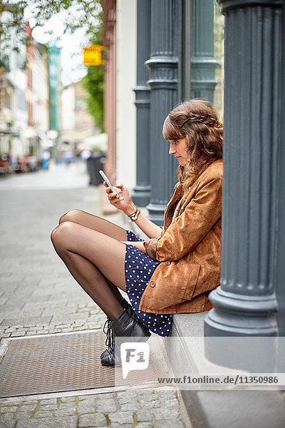 Junge Frau schaut auf ihr Handy
