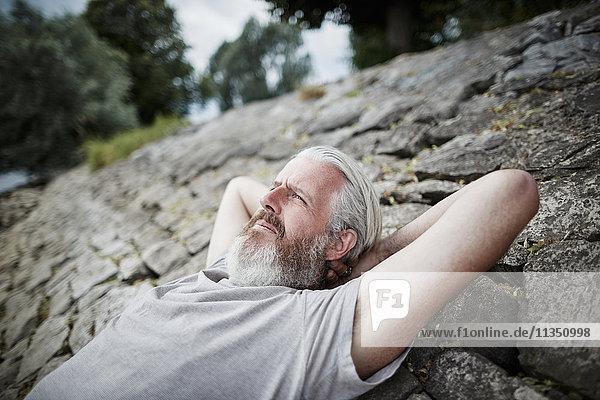 Entspannter reifer Mann mit Vollbart am Flussufer