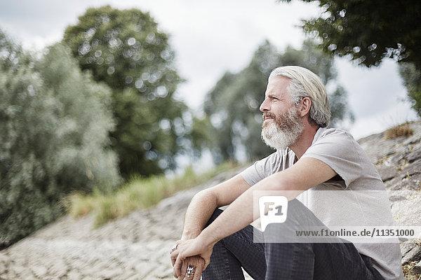 Reifer Mann mit Vollbart sitzt am Flussufer