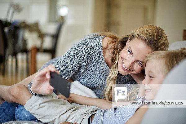 Fröhliche Mutter und Sohn schauen auf ein Handy