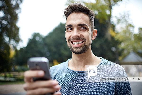 Portrait eines lächelnden jungen Mannes mit Handy im Freien