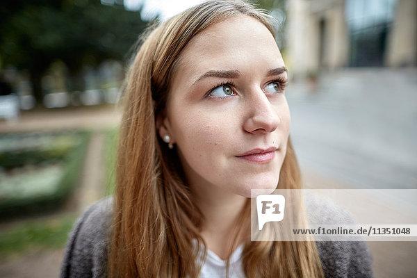 Portrait einer nachdenklichen jungen Frau im Freien