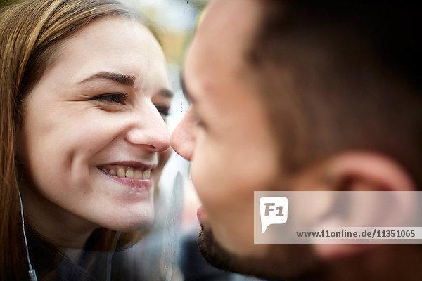Glückliches junges Paar mit Glasscheibe zwischen sich