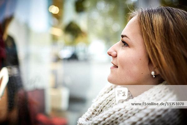 Lächelnde junge Frau schaut in ein Schaufenster