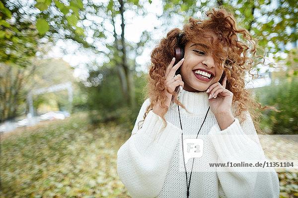 Fröhliche Teenagerin mit Kopfhörern im Park
