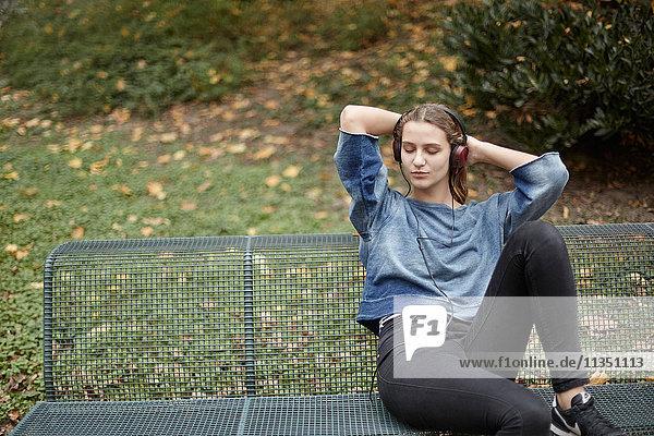 Junge Frau mit geschlossenen Augen und Kopfhörern auf einer Parkbank