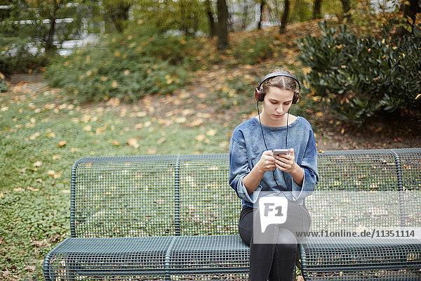Junge Frau mit Kopfhörern auf einer Parkbank schaut auf ihr Handy