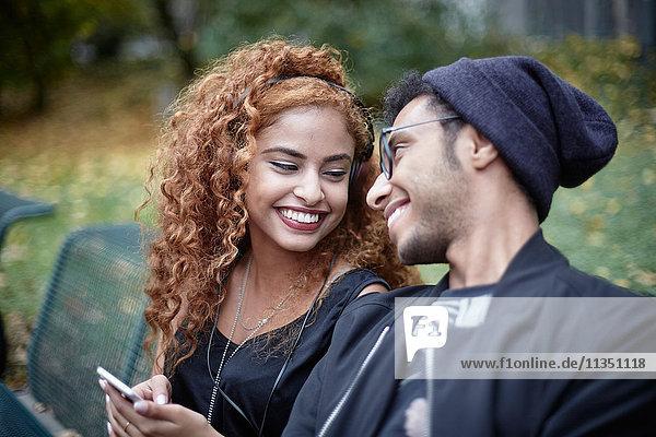 Lächelndes junges Paar mit Handy auf einer Parkbank