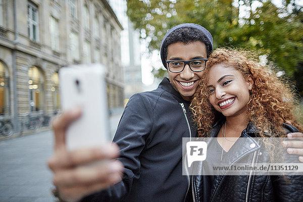 Lächelndes junges Paar macht ein Selfie im Freien
