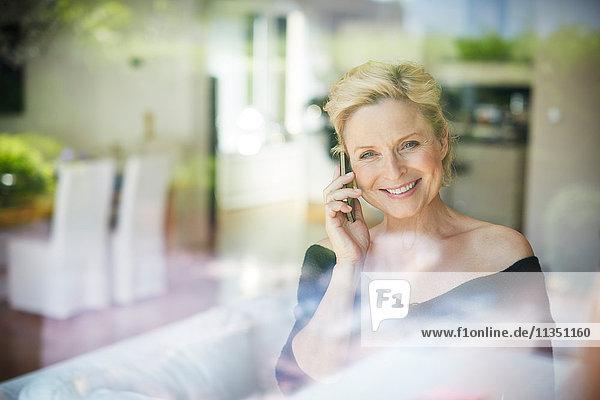 Lächelnde reife Frau telefoniert hinter Fenster