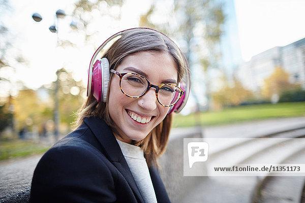 Portrait einer fröhlichen Frau mit Kopfhörern im Freien