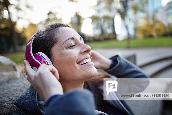 Lächelnde Frau mit Kopfhörern im Freien