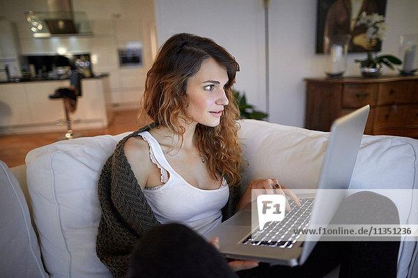 Frau sitzt auf der Couch und schaut auf ihren Laptop