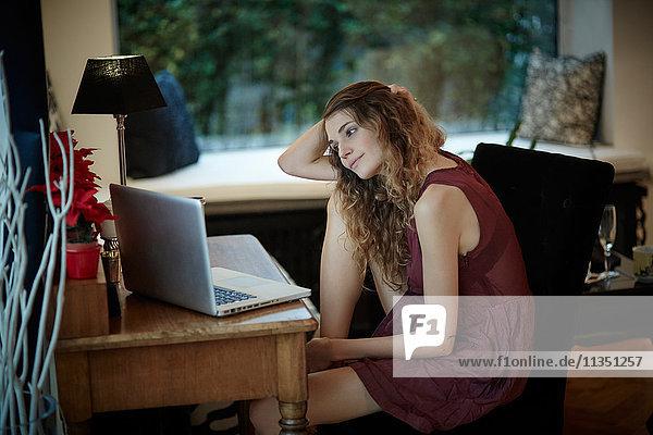 Frau sitzt auf einem Stuhl am Tisch und schaut auf ihren Laptop