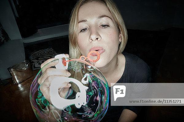 Frau macht eine große Seifenblase