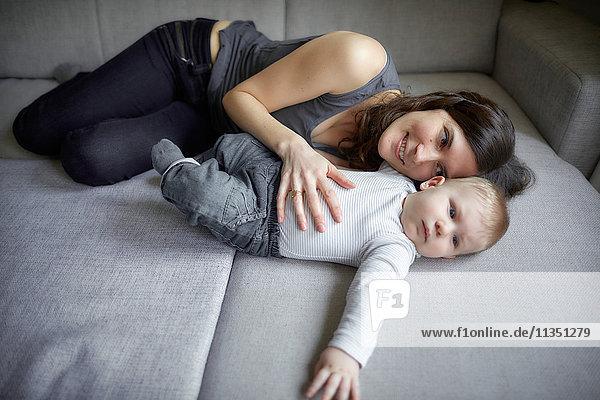 Mutter und Baby liegen auf der Couch