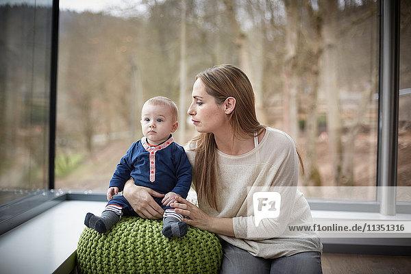 Mutter mit Baby auf einem Sitz Zuhause