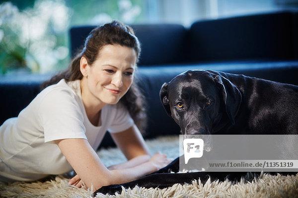 Frau liegt mit Hund auf dem Teppich