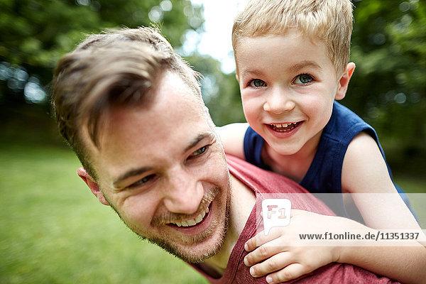Glücklicher Vater trägt seinen Sohn huckepack