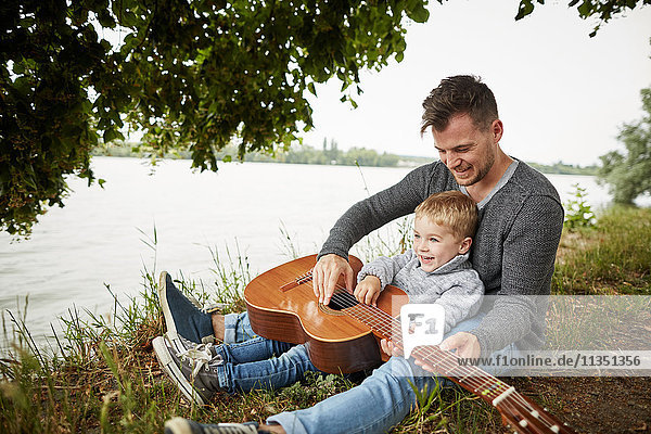 Glücklicher Vater und Sohn sitzen mit Gitarre am Flussufer