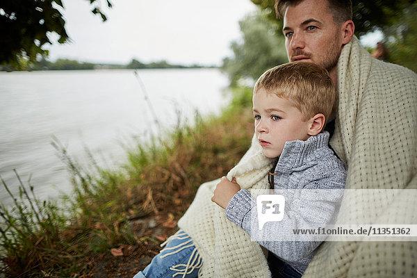 Vater und Sohn sitzen am Flussufer eingewickelt in eine Decke