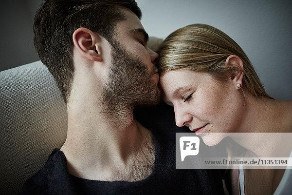 Junges Paar schmust auf der Couch