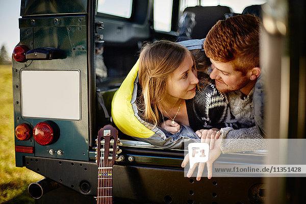 Junges Paar liegt mit einem Schlafsack im Auto