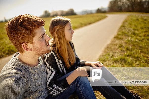 Junges Paar sitzt an einem Feldweg