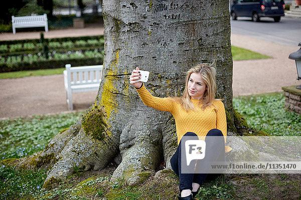 Junge Frau an einem Baumstamm macht ein Selfie