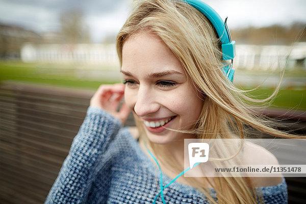 Glückliche junge Frau mit Kopfhörern auf einer Bank