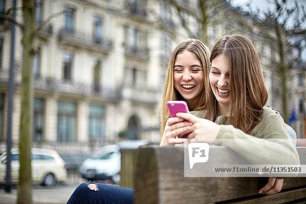 Zwei fröhliche junge Frauen mit Handy