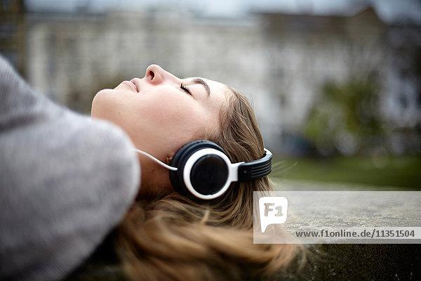 Entspannte liegende junge Frau mit Kopfhörern
