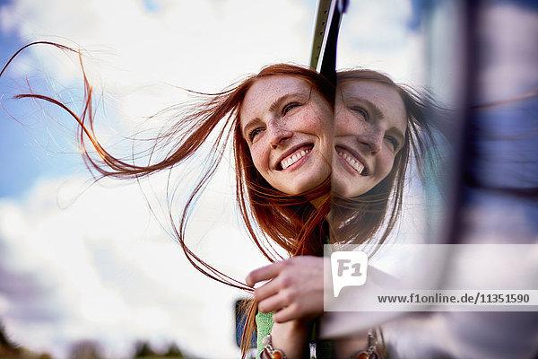 Lächelnde junge Frau lehnt sich aus dem Autofenster