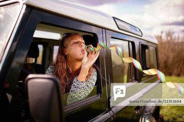 Junge Frau bläst eine Luftschlange aus einem Auto