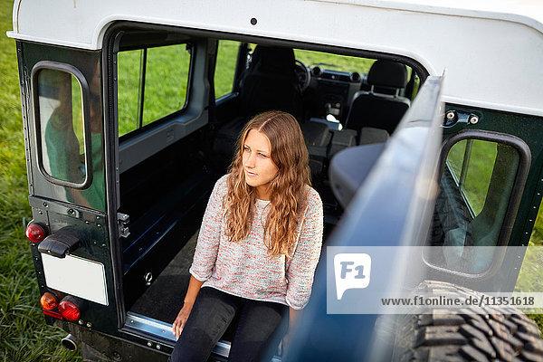 Junge Frau sitzt im Kofferraum eines Geländewagens auf einer Wiese geparkt