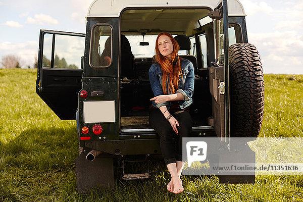 Junge Frau sitzt im Kofferraum eines Geländewagens auf einer Wiese