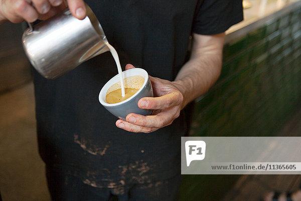 Männliche Baristas Hände strömen Milch in Kaffeetasse im Cafe