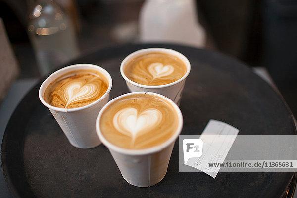 Drei Mitnehmen Tasse Kaffee mit herzförmigen Spitzen
