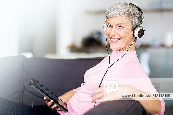 Seniorin mit Köpfhörern und Tablet PC