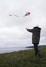 Mann Kite an windigen Küste im Herbst fliegen zu lassen