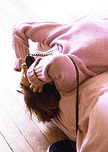 Frau auf Bett liegend mit Telefon in der hand und Kopf hängen aus Bett
