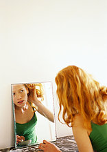 Frau blickt auf Reflektion im Spiegel, ihr Haar zurück ziehen.