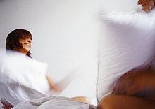 Frau und Mann mit Pillowfight, verschwommen.