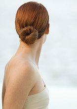 Frau mit roten Haaren in Bun und schulterfreies Top, Rückansicht