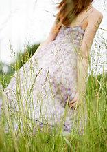 Junge Frau zu Fuß durch Gras, Kleid in Wind weht